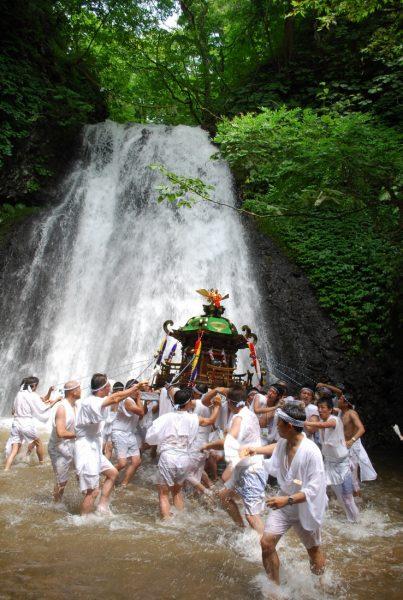 Local men carry the mikoshi into Shirataki Falls in Happo Town.