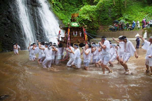 Local men carry the mikoshi into the waterfall.