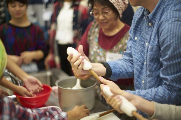 Molding the pounded rice around a stick to make kiritanpo.
