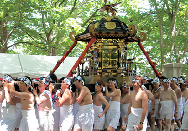 Locals carrying a mikoshi during a festival.